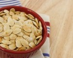 Toasted pumpkin seeds in a red bowl with copy space