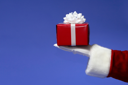 Santa Holding Red and White Christmas Gift on Blue
