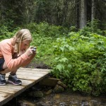 young-girl-taking-photo-outdoors-forest-31578571