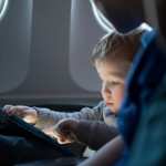 Little boy traveling in an airplane sitting in his seat playing with a tablet computer watched by a parent