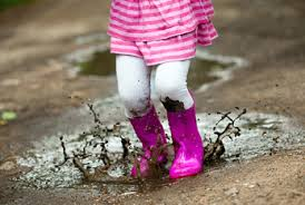 child splashing in puddles