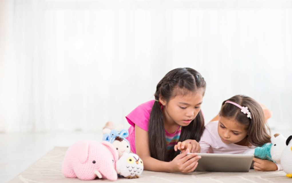 Girls playing on tablet apps for tweens