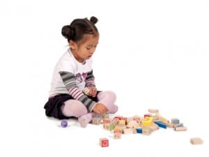 female kid playing wooden blocks