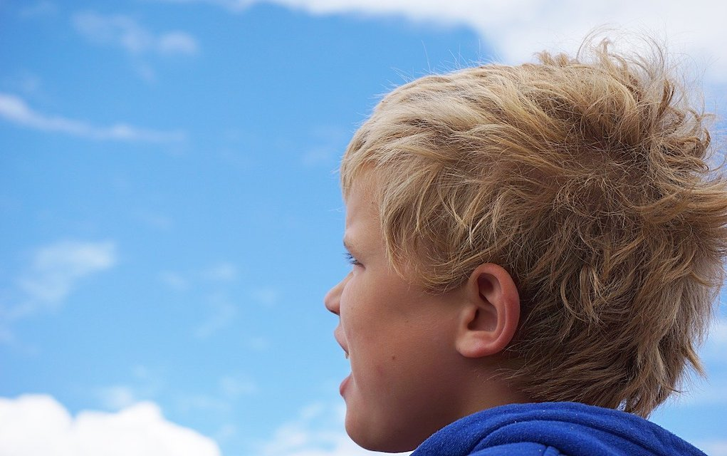 child watching clouds