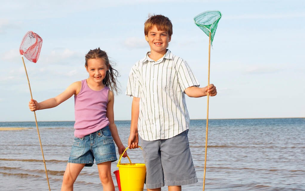 Girl and boy fishing at the beach
