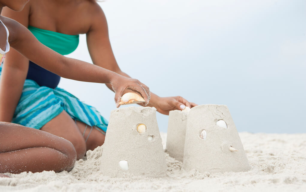 Child building sand castles on the beach