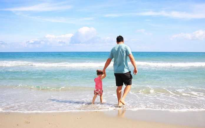 Dad and daughter on the sand for Things to do at the beach