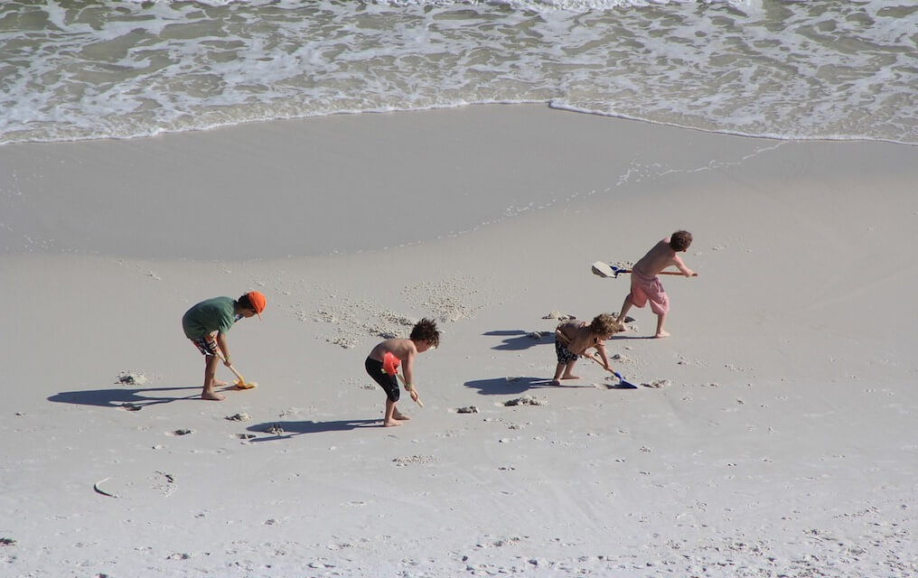Kids digging in the sand for things to do at the beach