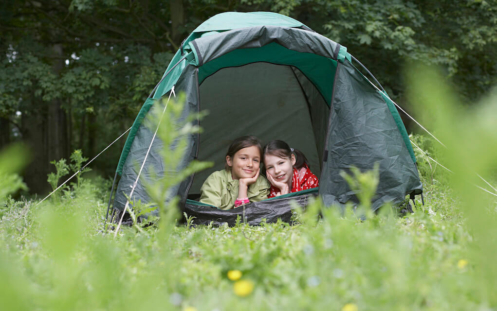 Two girls in a tent for camping with kids Family friendly campsites in Ireland with activities