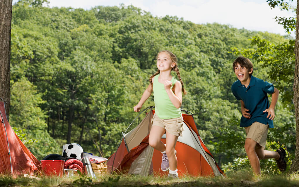 Girl and boy running at campsite for camping with kids