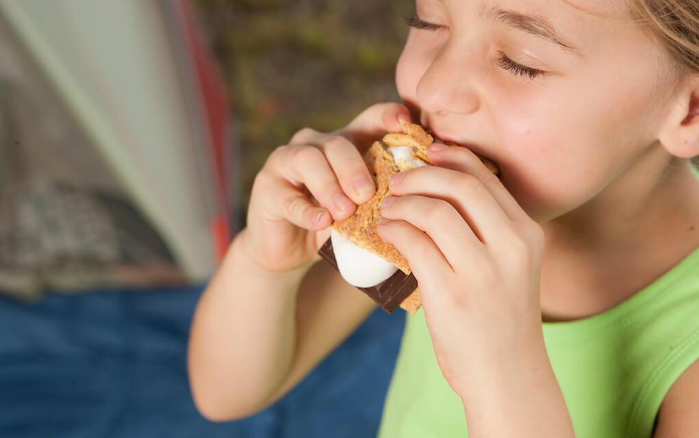 Girl eating smore for camping with kids