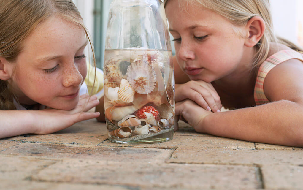 Two girls looking at shells in a jar for beach craft ideas
