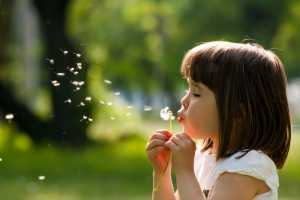 child outside blowing dandelions