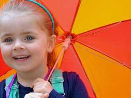 rainy day fun little girl with a striped umbrella