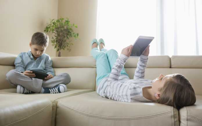 Children lying on couch with tablets for online safety for kids - Mykidstime