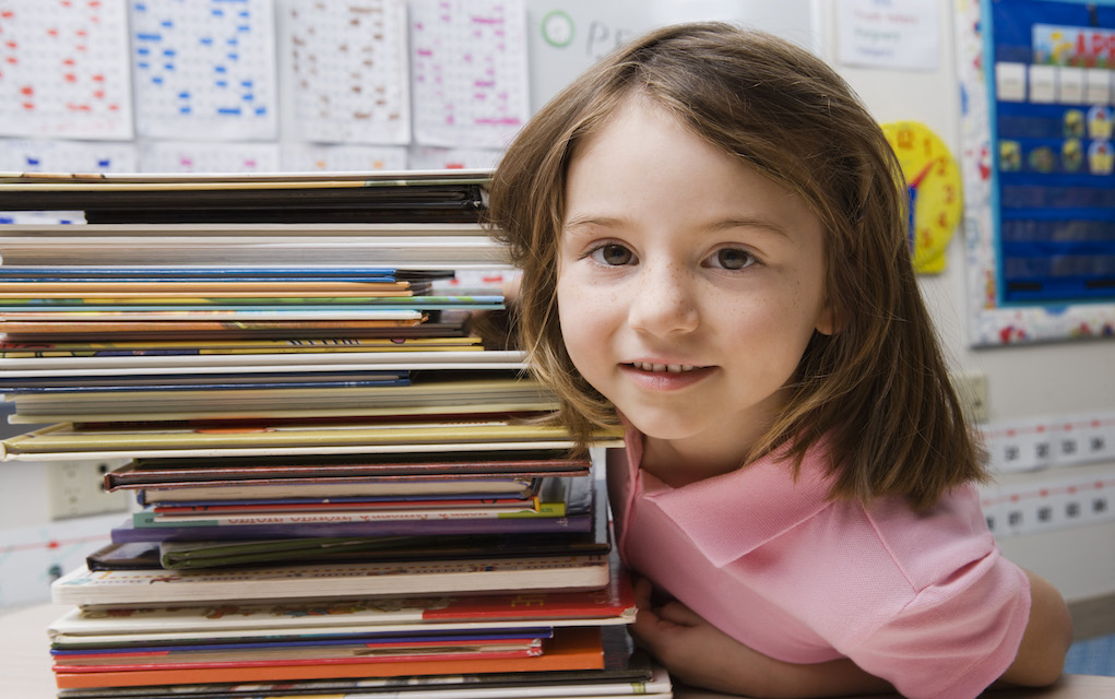 Girl with school books money saving tips on tips for buying school books