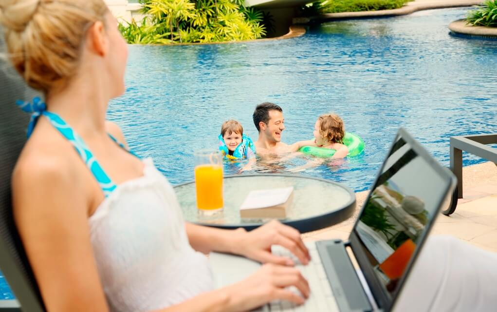 Mum on laptop watching family having fun in the pool for grow your business