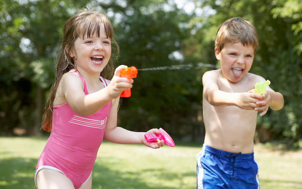 girl and boy having a water fight for photographing kids