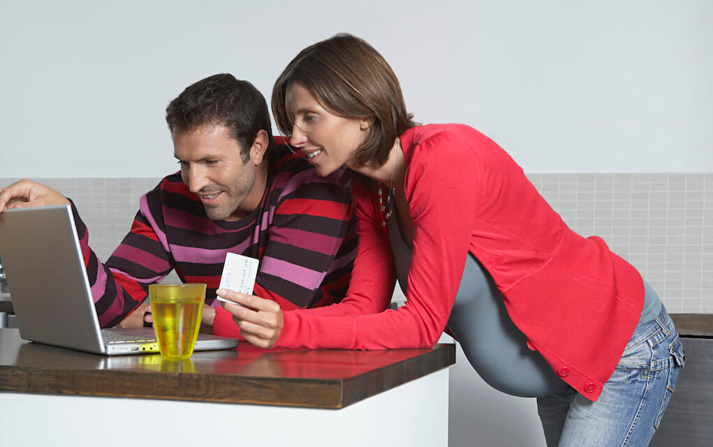 Man and pregnant woman looking at laptop