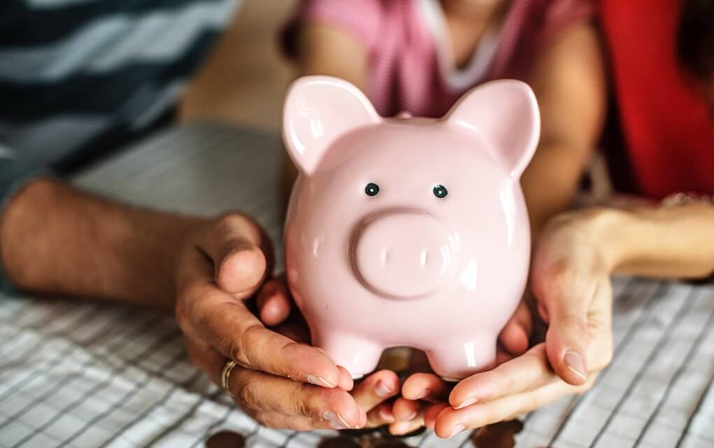 Parents and child with piggy bank for pocket money