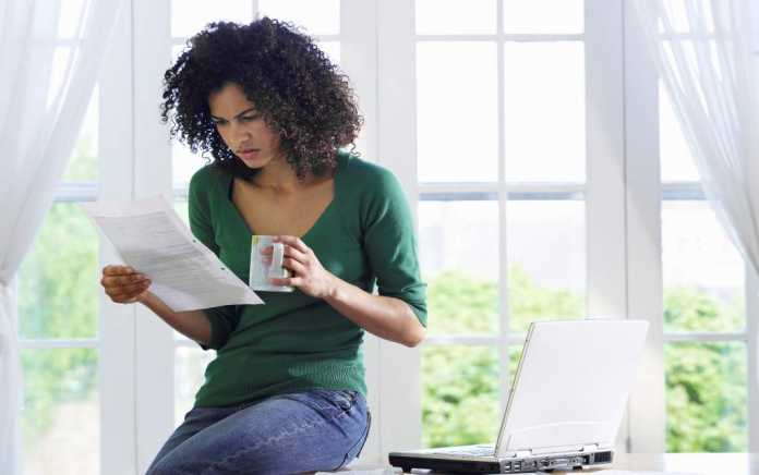 woman looking at energy bill money saving tips on buying school books