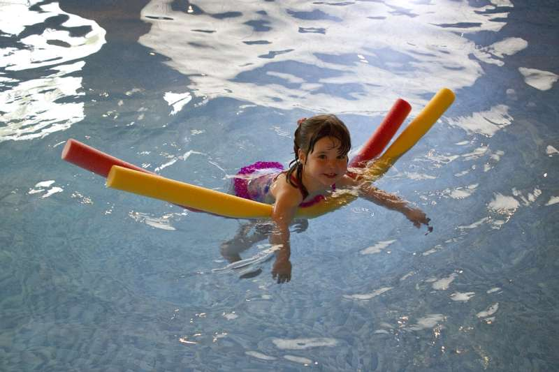 child with pool noodles